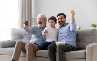 A multigenerational family happily watching the super bowl on their couch, to illustrate the top 3 Super Bowl commercials, written by Joanne Tan, 10PlusBrand.com
